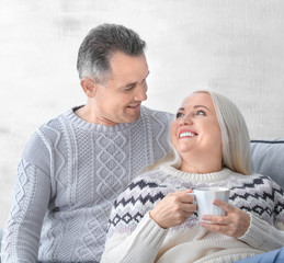 Happy mature couple drinking tea at home