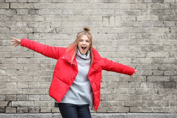 Attractive hipster girl in red jacket near brick wall outdoors