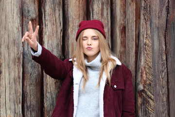 Attractive hipster girl near wooden fence outdoors