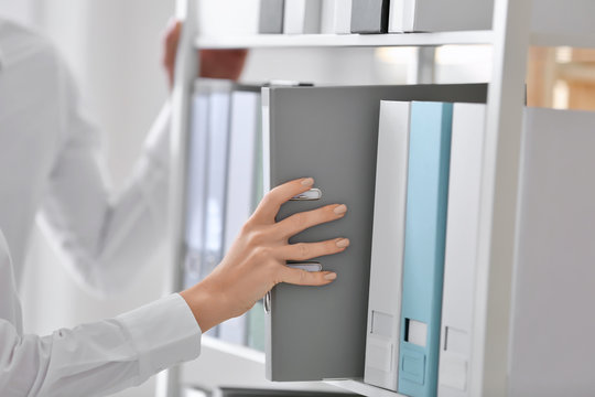 Young woman taking folder with documents from shelf in archive