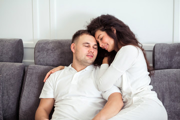 Loving young couple in white clothes hugging and relaxing on sofa at home