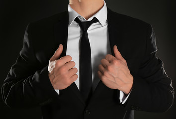 Handsome man in formal suit on dark background, closeup
