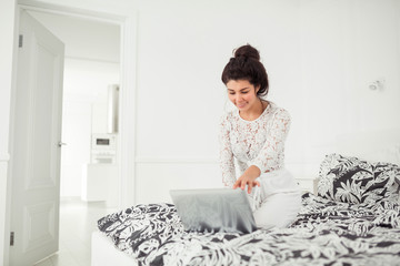 Young woman working with laptop at home, online business. Smiling woman sitting on bed, relaxing, browsing internet or online shopping, free time at home.