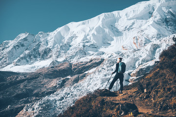 Standing young woman with backpack on the mountain peak and looking on beautiful mountains and glacier at sunset. Landscape with girl, rocks with snowy peaks,blue sky in Nepal.Hiking, travel. Vintage