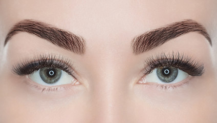 Procedure for eyelash extension. Beautiful woman with long eyelashes in a beauty salon. Look at the camera.