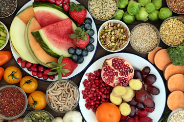 Health food concept with fresh fruit, vegetables, seeds, pulses, grains and cereals with foods high in vitamins, minerals, anthocyanins, antioxidants and fibre, top view.