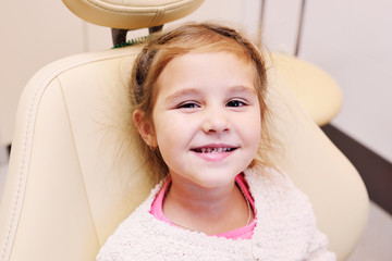 little baby girl with dental caries on the teeth in the dental chair on the teeth in the dental chair