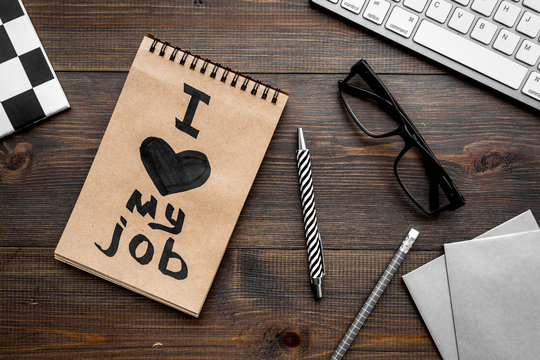 Positive attitude to work. I love my job written in notebook at office desk on dark wooden background top view