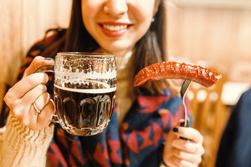 Young happy woman eats fried sausage and drinks mug of beer at bar