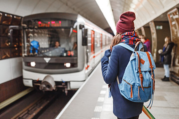Rear view of a woman backpacker waiting for train arrival in metro or subway
