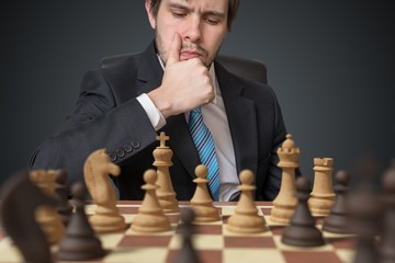 Young businessman is thinking and playing chess.