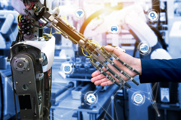 Cyber communication and robotic trend and artificial intelligence concepts. Industrial 4.0 Cyber Physical Systems concept. Robot and Engineerer human holding hand with handshake and graphic.