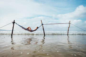 Woman relax lying in hammock swing over the ocean surf line