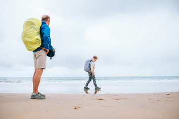 Traveling with child: father and son enjoyed empty ocean beach