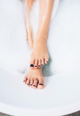 well groomed woman's legs with black pedicure in bathtub