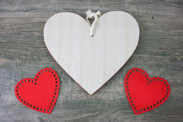 Rustic Wooden Heart and Red Cloth Hearts Over Wood Background for Valentine's Day Holiday with Copy Space