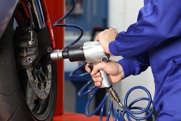 Mechanic hand using a pneumatic gun to loosen a nut