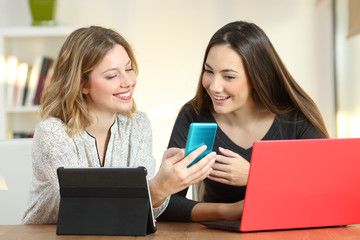 Two friends using multiple devices at home