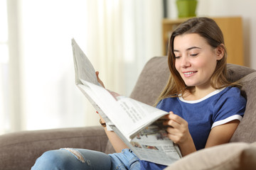 Teen reading a newspaper on a sofa at home