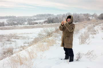Smiling woman is taking pictures on mobile phone. Winter landscape on snowy meadow. Beautiful frost on trees and plants