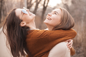 Two cute young women are hugging and laughing outdoors