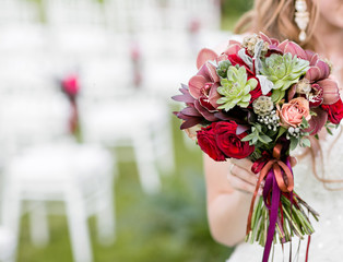 Stunning red bridal bouquet on white chair. Wedding ceremony. Mix of succulents, orchids and roses. copy space