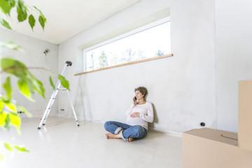 Schwangere Frau  sitzt auf dem Boden auf der Baustelle im Haus und telefoniert