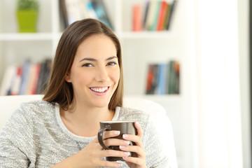 Woman holding a coffee mug posing at home