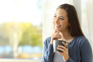Woman thinking looking at side at home