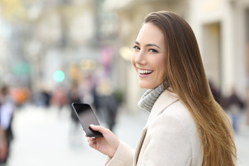 Woman using a phone and looking at camera in winter