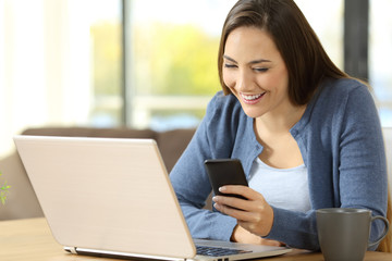 Woman using a phone and laptop sitting at home