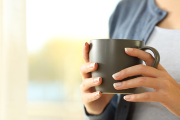 Woman hands holding a coffee mug at home