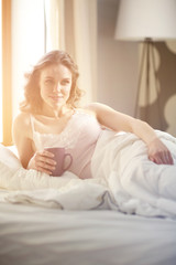 Young woman drinking cup of coffee or tea while lying in bed.