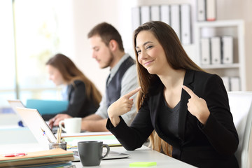 Proud businesswoman pointing himself at office