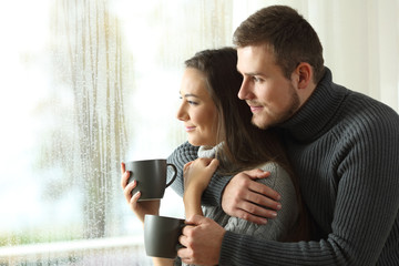 Couple looking through a window in a rainy day