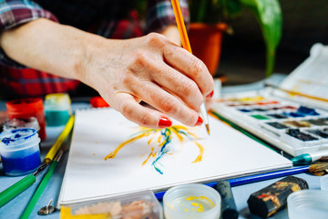 woman artist paints with a brush and bright watercolor paints on white paper