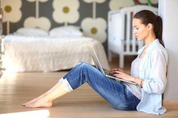 Young woman sitting on the floor near children's cot with laptop. Young mom