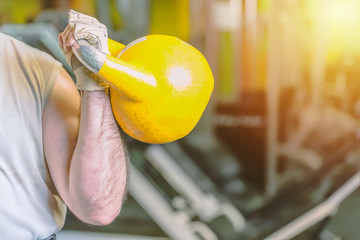 Strong male hand with yellow kettlebell in gym fitness sports center. Sports concept