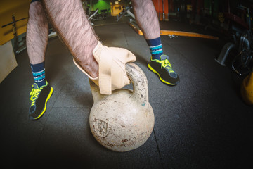 Strong male hand with grey kettlebell in gym fitness sports center. Sports concept