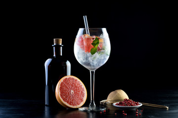 gin and tonic alcohol drink cocktail glass ice fruit garnish plain black white background