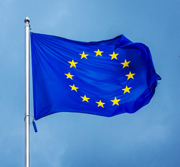 The flag of the European Union , against the background of the sunny sky.