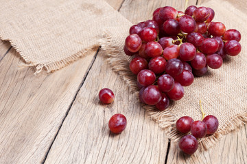 Red grapes on old wooden table background. Fototapete