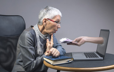 Senior old lady being lured into an online scam that promises easy money, money fraud concept