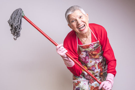 Cleaning senior lady crazy and frustrated, threatening to beat you with a mop