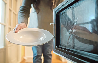 Housewife looking at dish into oven in kitchen. View from inside of the oven
