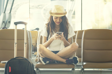 Young woman in airport waiting for air travel using smart phone. She is sitting with travel suitcase trolley, in waiting hall of departure lounge in airport.