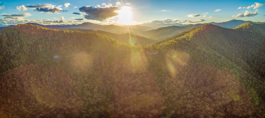Aerial panorama of native Australian forest and mountains at sunset with sun flare
