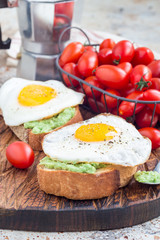 Open sandwiches with mashed avocado and fried egg on bread, vertical