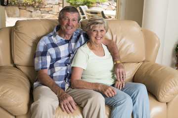 senior beautiful middle age couple around 70 years old smiling happy together at home living room sofa couch looking sweet in lifetime love