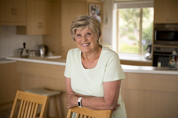 beautiful portrait of pretty and sweet senior mature woman in middle age around 70 years old smiling happy and friendly at home kitchen
